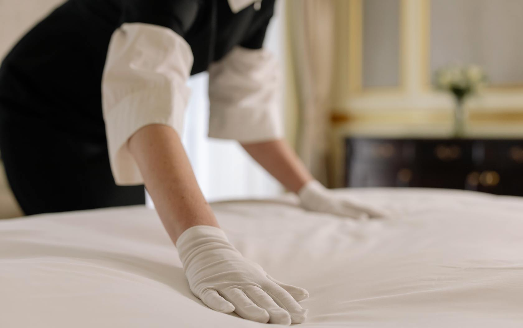 Housekeeper making a bed.